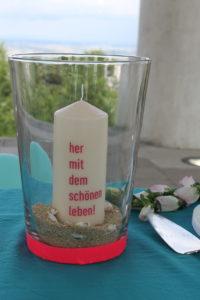 weiße Kerze mit Beschriftung für eine Willkommensfeier