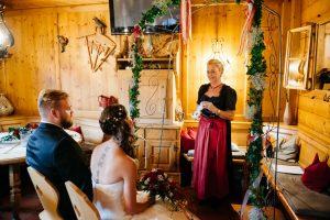 Freie Rednerin im Dirndl mit Brautpaar sitzend im Bergstadl in Hinterglemm